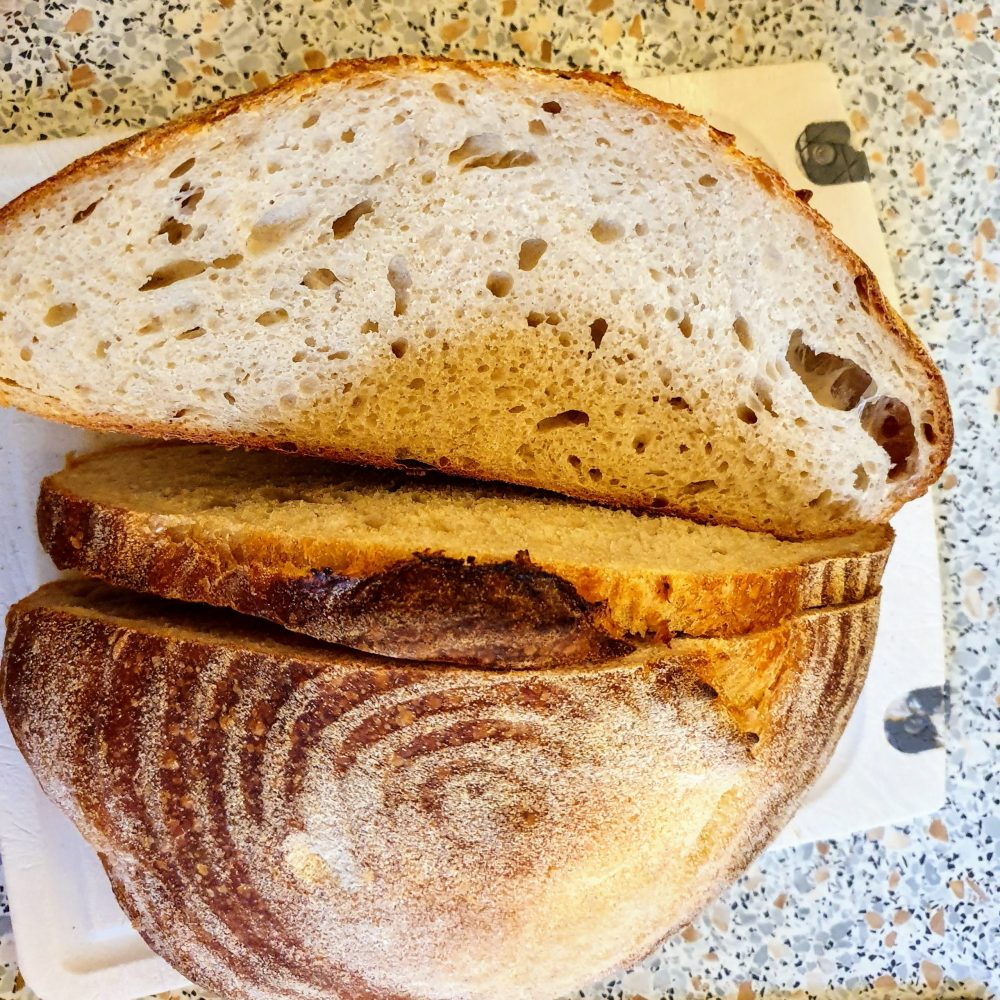 Sourdough loaf cut and ready to be eaten. It won't last long.