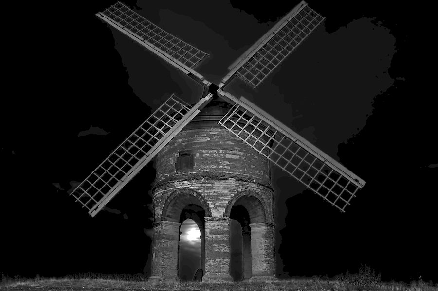 Chesterton Windmill with the moon in clouds under one arch.
