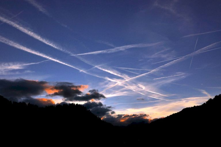 Sunset clouds and vapour trails at Les Moulins, Switzerland.