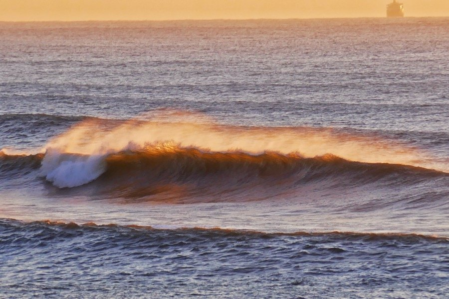 The early morning sun catching the top of a breaking wave in the sunrise at Umdloti.