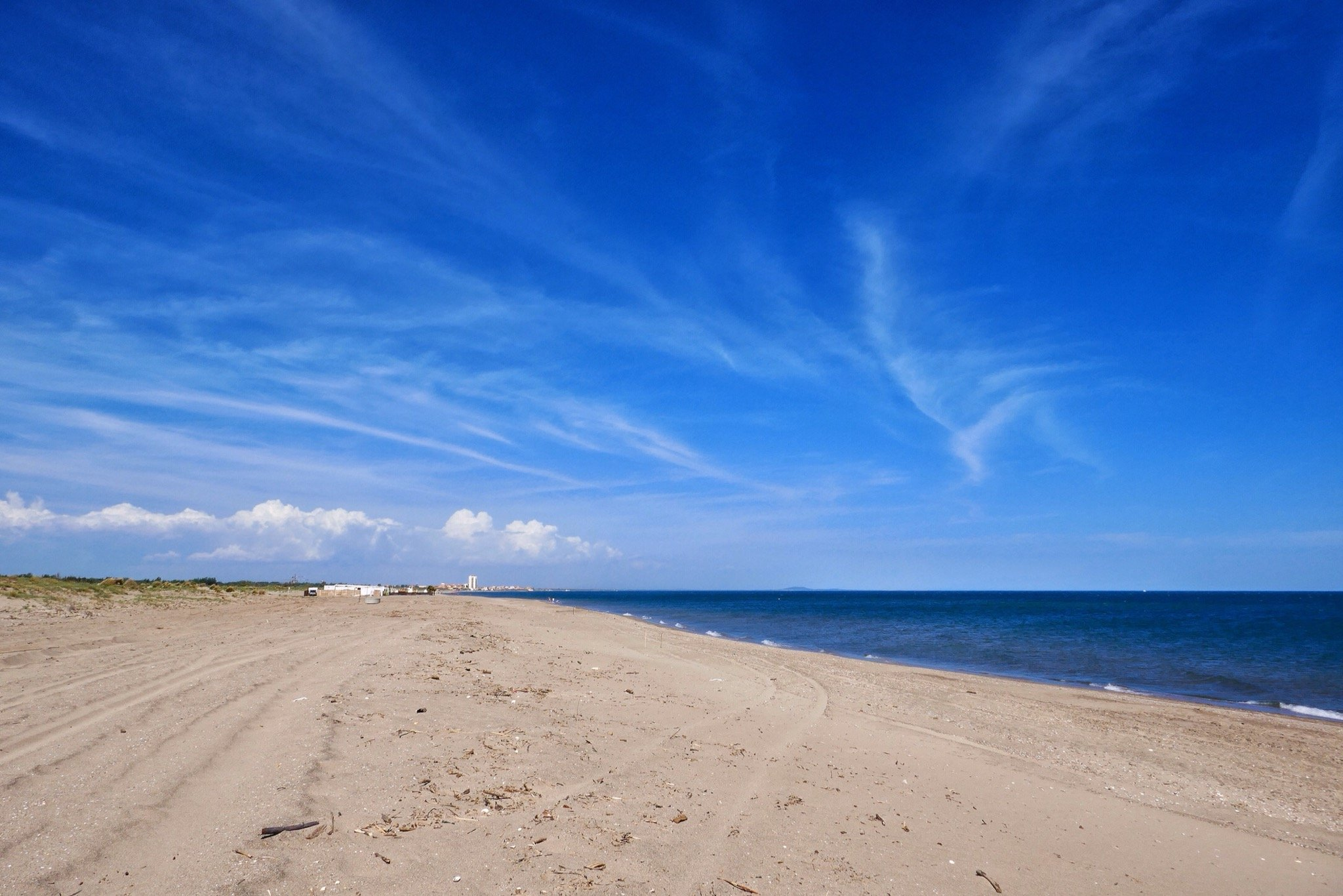 A view of Beach and sky with Valras Plage on the horizon. Near Blue Bayou., Valras Plage, France.